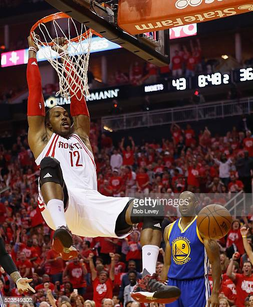 Dwight Howard of the Houston Rockets puts back a missed shot for a dunk as Andre Iguodala of the Golden State Warriors looks on at Toyota Center on...