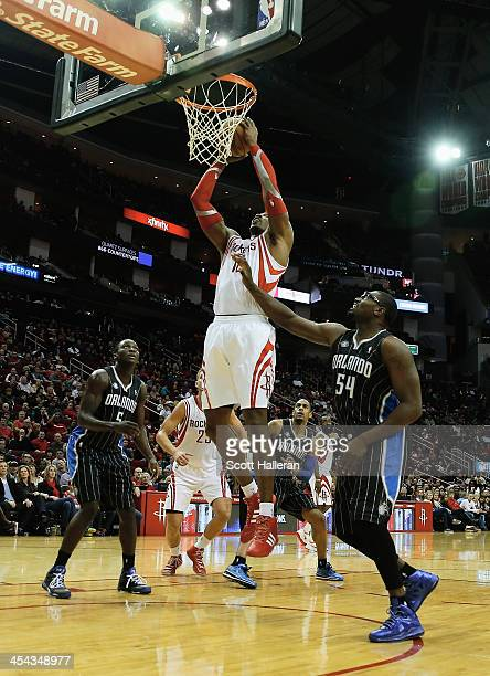 Dwight Howard of the Houston Rockets takes a shot over Jason Maxiell of the Orlando Magic at Toyota Center on December 8 2013 in Houston Texas NOTE...