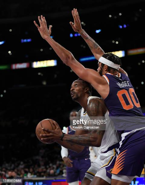 Dwight Howard of the Los Angeles Lakers is defended by JaVale McGee Phoenix Suns during the first half of a preseason game at Staples Center on...