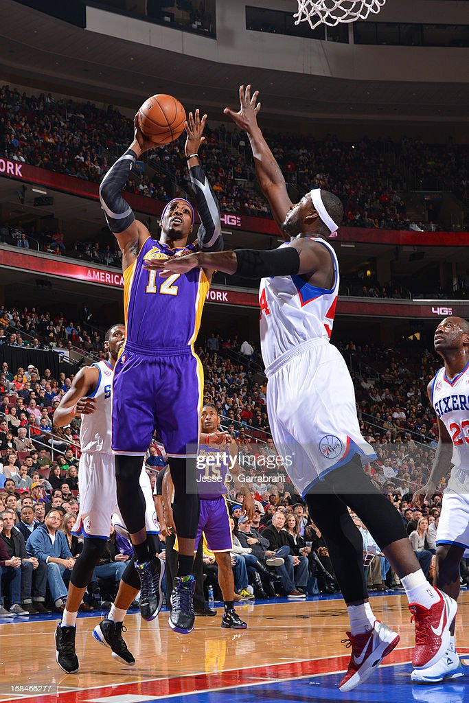 Dwight Howard #12 of the Los Angeles Lakers shoots against Kwame Brown #54 of the Philadelphia 76ers on December 16, 2012 at the Wells Fargo Center in Philadelphia, Pennsylvania.