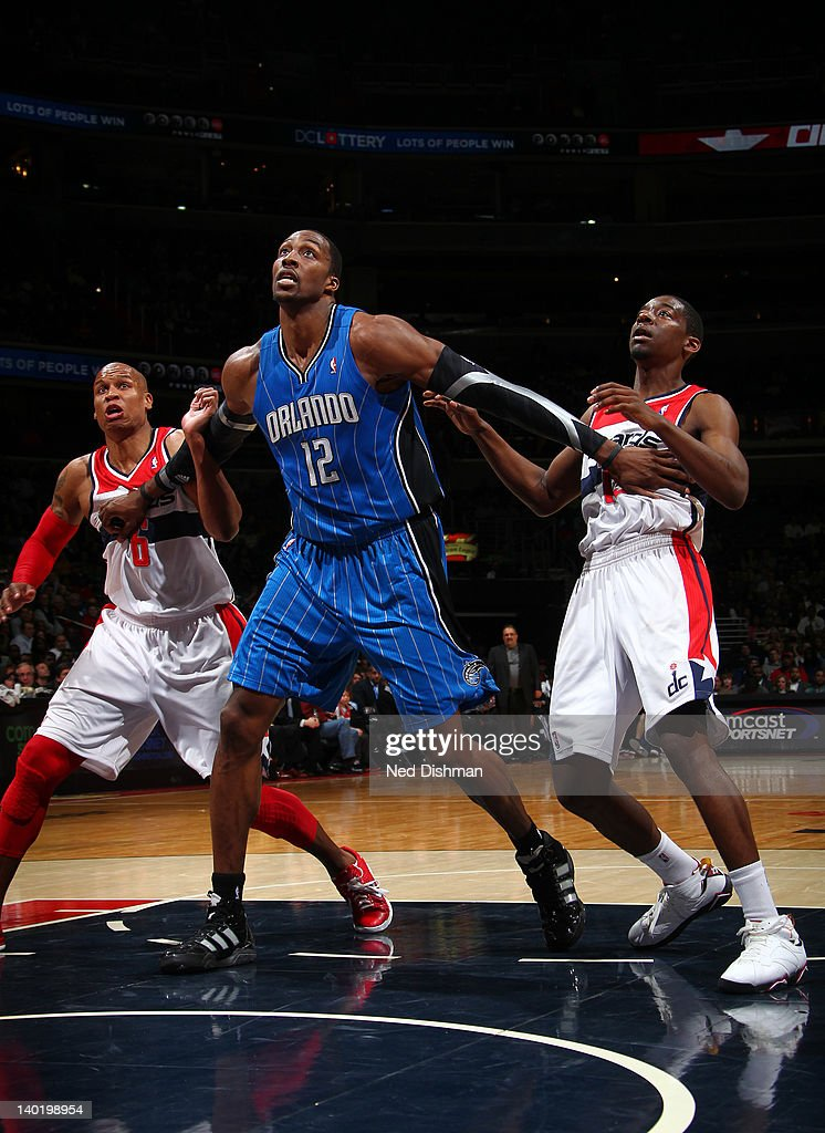 Dwight Howard #12 of the Orlando Magic battles for position against Maurice Evans #6 and Jordan Crawford #15 of the Washington Wizards during the game at the Verizon Center on February 29, 2012 in Washington, DC.