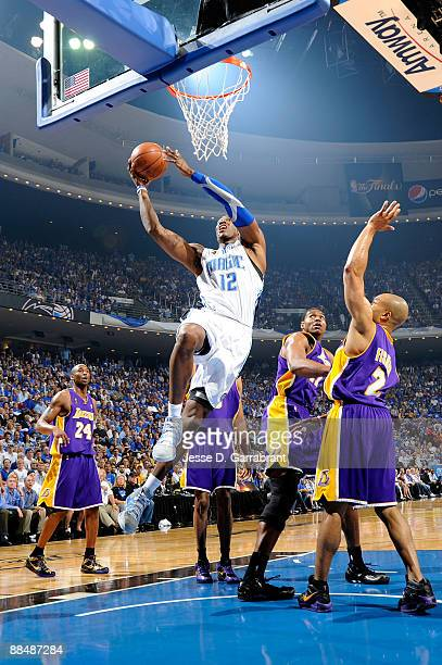 Dwight Howard of the Orlando Magic drives for a shot attempt against Derek Fisher Andrew Bynum and Kobe Bryant of the Los Angeles Lakers in Game Five...