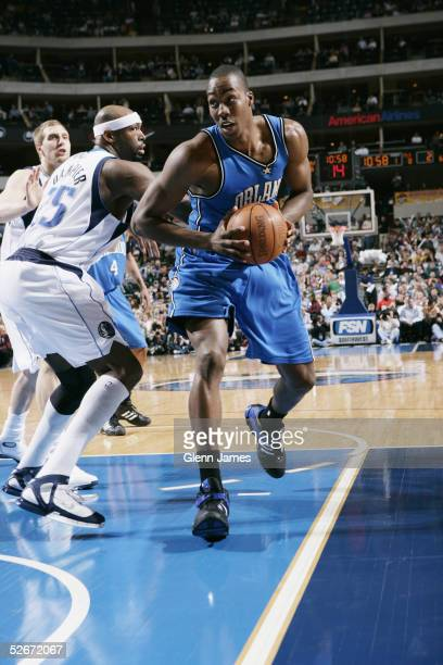 Dwight Howard of the Orlando Magic drives to the basket past Erick Dampier of the Dallas Mavericks during the game at American Airlines Arena on...