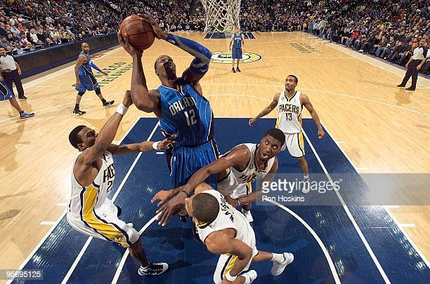 Dwight Howard of the Orlando Magic goes to the basket against Brandon Rush and Roy Hibbert of the Indiana Pacers during the game on January 5 2010 at...