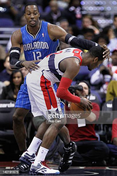 Dwight Howard of the Orlando Magic guards John Wall of the Washington Wizards during the first half at the Verizon Center on February 29 2012 in...