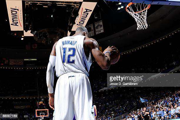 Dwight Howard of the Orlando Magic holds the ball as he stands on court against the Los Angeles Lakers in Game Three of the 2009 NBA Finals at Amway...
