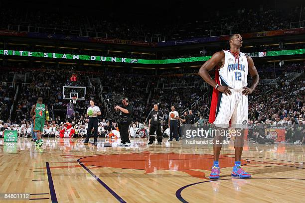 Dwight Howard of the Orlando Magic looks on as Nate Robinson of the New York Knicks walks towards half court during the Sprite Slam Dunk Contest on...