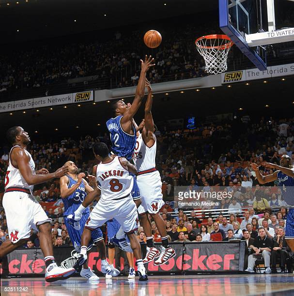 Dwight Howard of the Orlando Magic puts a shot up against Kurt Thomas and Jermaine Jackson of the New York Knicks at TD Waterhouse Centre on March 4...