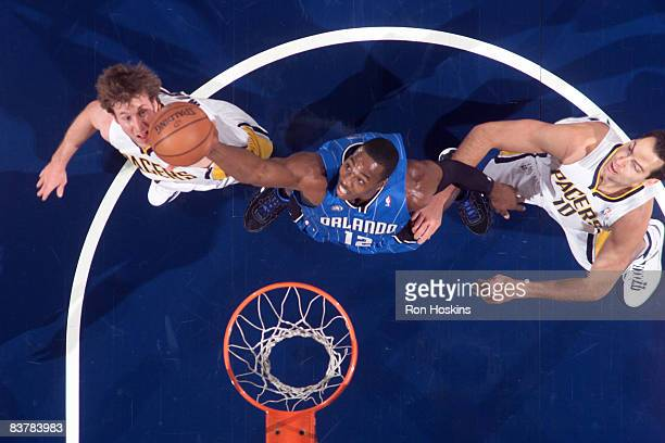 Dwight Howard of the Orlando Magic rebounds over Troy Murphy and Jeff Foster of the Indiana Pacers at Conseco Fieldhouse on November 21 2008 in...