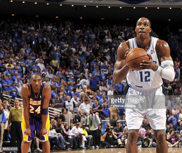 Dwight Howard of the Orlando Magic shoots a free throw as Kobe Bryant of the Los Angeles Lakers looks on in Game Three of the 2009 NBA Finals at...