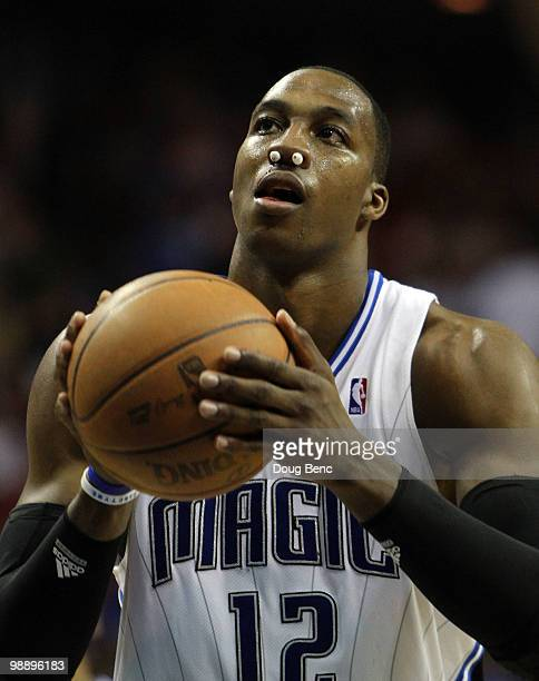 Dwight Howard of the Orlando Magic shoots free throws after being hit in the nose causing team trainers to plug his nose until he could be taken to...