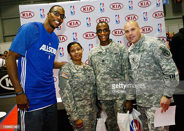 Dwight Howard Signs poses with soldiers during an autograph session in the Kia MVP court at Jam Session during NBA All Star Weekend on February 25,...
