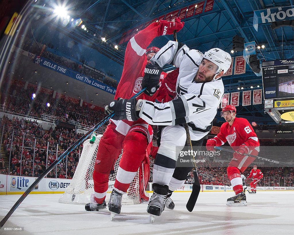 Dwight King #74 of the Los Angeles Kings and Danny DeKeyser #65 of the Detroit Red Wings battle for the puck behind the net during an NHL game at Joe Louis Arena on December 15, 2016 in Detroit, Michigan. The Kings defeated the Wings 4-1.