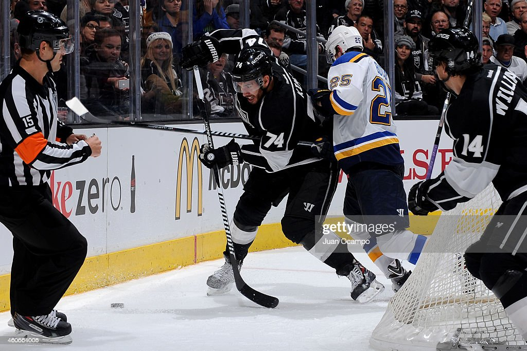 Dwight King #74 of the Los Angeles Kings attempts to retain possession of the puck against Chris Butler #25 of the St. Louis Blues during a game at STAPLES Center on December 18, 2014 in Los Angeles, California.
