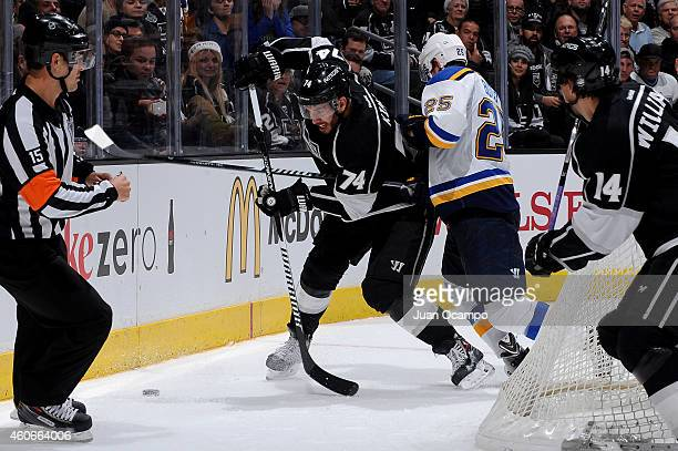 Dwight King of the Los Angeles Kings attempts to retain possession of the puck against Chris Butler of the St Louis Blues during a game at STAPLES...