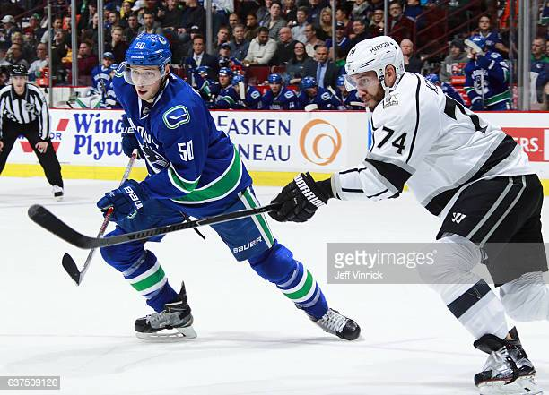 Dwight King of the Los Angeles Kings checks Brendan Gaunce of the Vancouver Canucks during their NHL game at Rogers Arena December 28 2016 in...