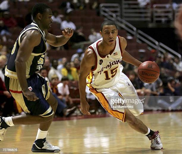 Dwight Lewis of the USC Trojans drives against Carl Elliott of the George Washington Colonials at the John R. Wooden Classic at the Honda Center...