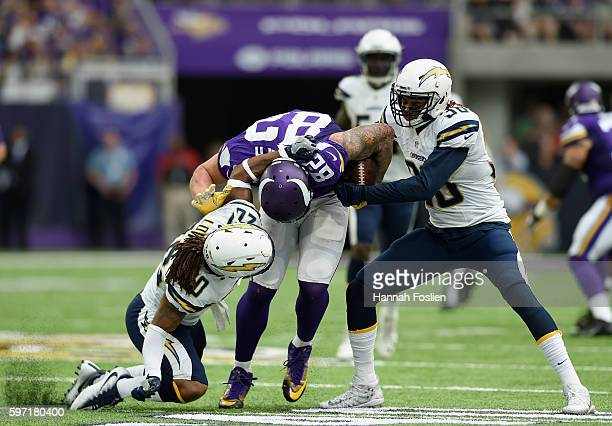 Dwight Lowery of the San Diego Chargers tackles Kyle Rudolph of the Minnesota Vikings as teammate Dexter McCoil forces a fumble during the second...