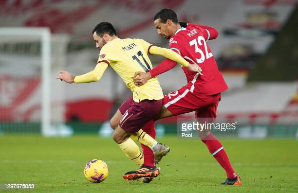 Dwight McNeil of Burnley battles for possession with Joel Matip of Liverpool during the Premier League match between Liverpool and Burnley at Anfield...
