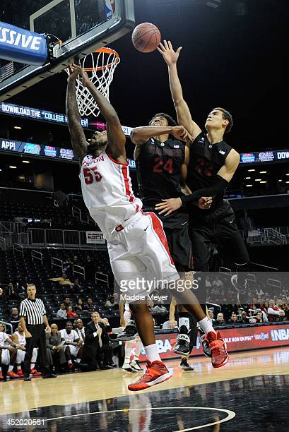 Dwight Powell of the Stanford Cardinal takes a shot over Josh Huestis and JJ Richardson of the Houston Cougars at Barclays Center on November 25 2013...