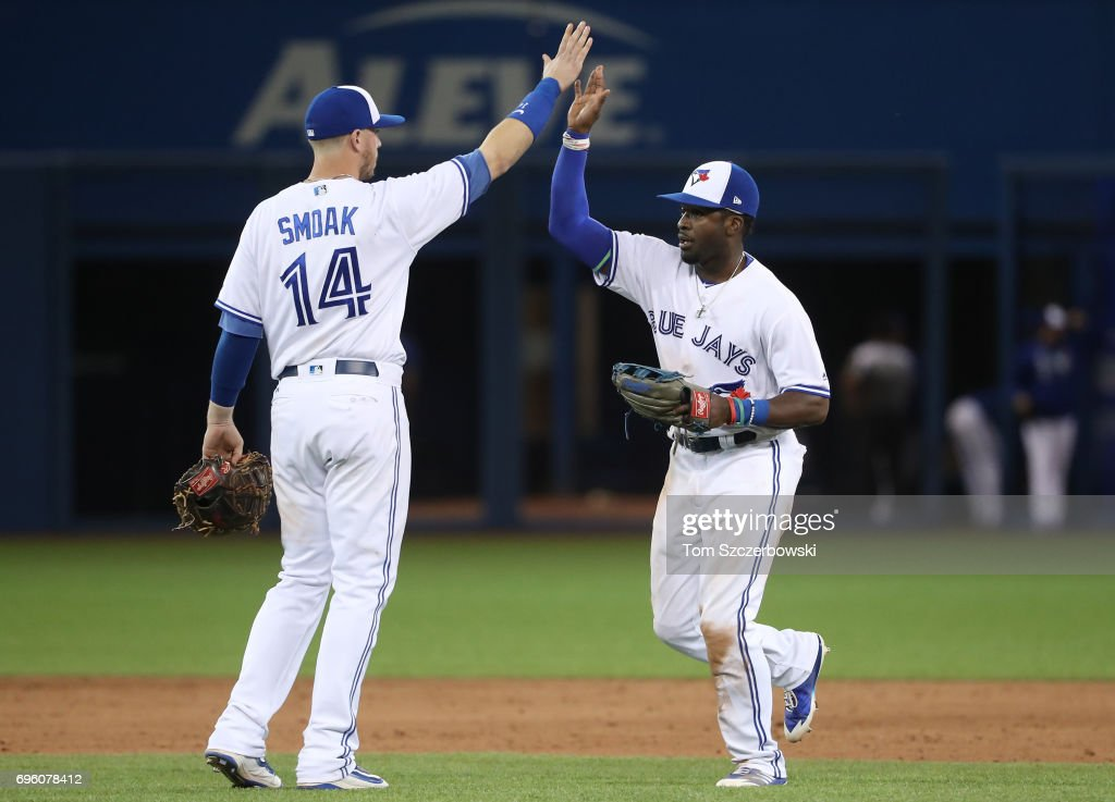Dwight Smith Jr. #15 of the Toronto Blue Jays celebrates their victory with Justin Smoak #14 during MLB game action against the Tampa Bay Rays at Rogers Centre on June 14, 2017 in Toronto, Canada.
