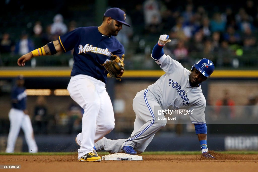 Dwight Smith Jr. #15 of the Toronto Blue Jays slides into second base for a double past Jonathan Villar #5 of the Milwaukee Brewers in the ninth inning at Miller Park on May 24, 2017 in Milwaukee, Wisconsin.