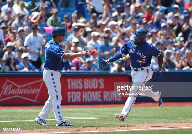 Dwight Smith Jr #27 of the Toronto Blue Jays is congratulated by third base coach Luis Rivera after hitting a solo home run in the sixth inning...
