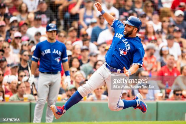 Mitch Moreland of the Boston Red Sox scores a run as Russell Martin of the Toronto Blue Jays fields a late throw in the sixth inning at Fenway Park...