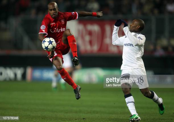 Dwight Tiendalli of Twente jumps for the ball next to Jermain Defoe of Tottenham during the UEFA Champions League Group A match between FC Twente and...