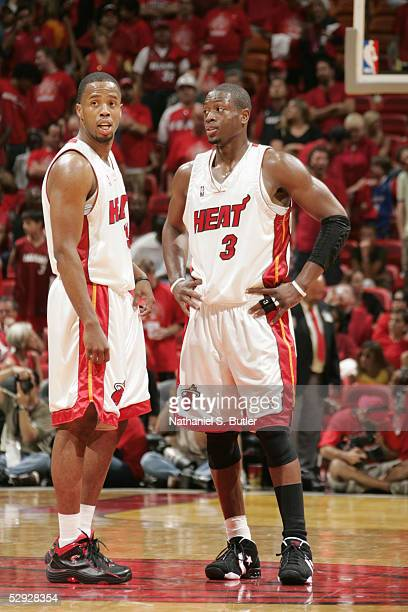 Dwyane Wade and Damon Jones of the Miami Heat have a discussion on the court during the game against the New Jersey Nets in Game one of the Eastern...