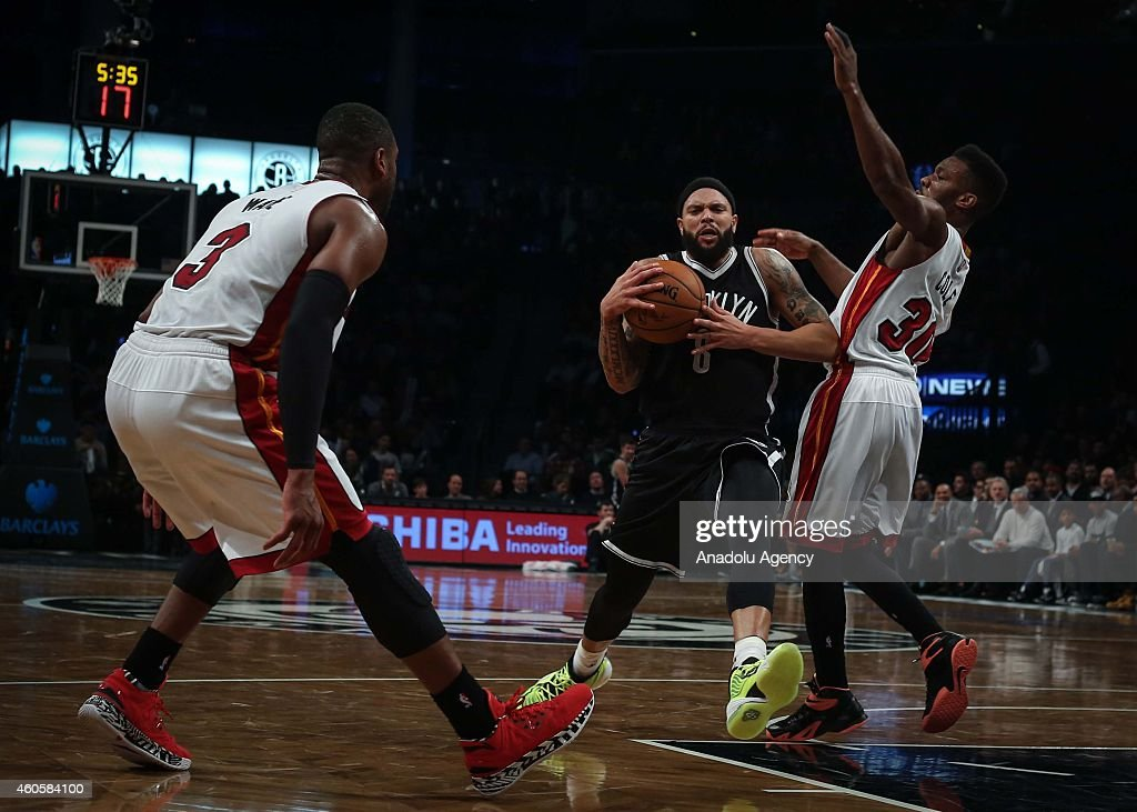 Dwyane Wade #3 and Norris Cole #30 of Miami Heat vie with Deron Williams #6 of Brooklyn Nets during a basketball game between Miami Heat and Brooklyn Nets at the Barclays Center on December 16, 2014 in the Brooklyn Borough of New York City.