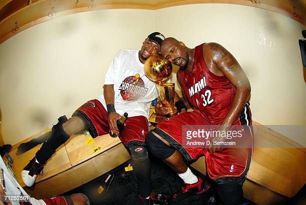 Dwyane Wade and Shaquille O'Neal of the Miami Heat celebrate in the locker room with the Larry O'Brien Championship trophy after their 9592 Game Six...