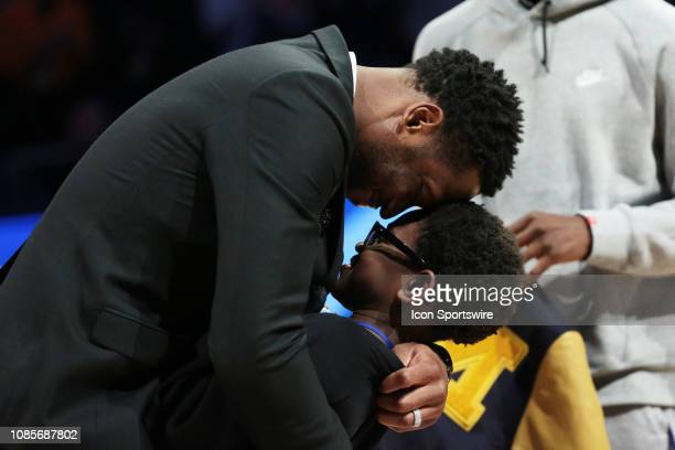 Dwyane Wade embraces his son Xavier during a halftime celebration during a game between the Marquette Golden Eagles and the Providence Friars at the...
