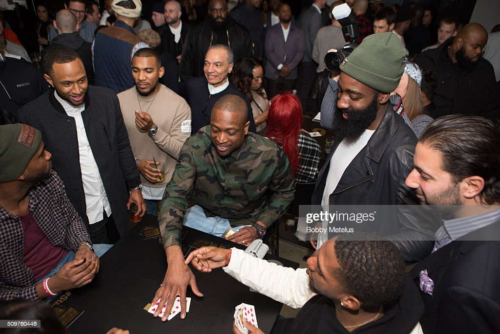 Dwyane Wade lays his cards down as James Harden looks over during the Dwyane Wade and Stance Stocks Spades Tournament at The One Eighty on February 11, 2016 in Toronto, Canada.