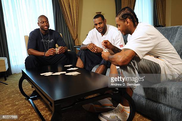 Dwyane Wade, LeBron James and Carmelo Anthony of the U.S. Men's Senior National Team play cards after practice for the Pre-Olympics USA Basketball...