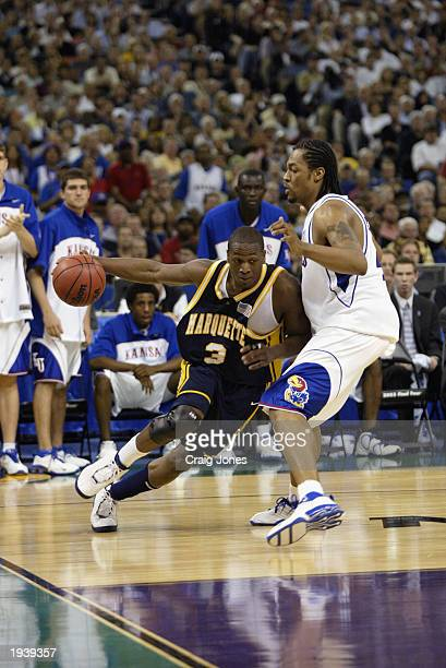 Dwyane Wade of Marquette University Golden Eagles drives around Jeff Graves of the University of Kansas Jayhawks during the semifinal round of the...