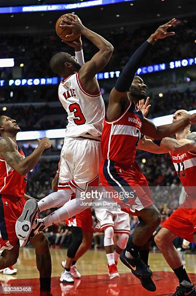 Dwyane Wade of the Chicago Bulls gets off a shot over John Wall of the Washington Wizards at the United Center on December 21 2016 in Chicago...