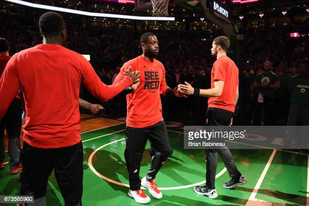 Dwyane Wade of the Chicago Bulls high fives with his teammates before the game against the Boston Celtics during Game Five of the Eastern Conference...