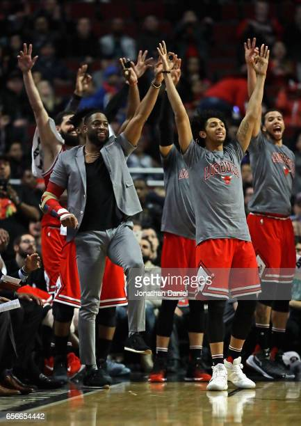 Dwyane Wade of the Chicago Bulls injured last week joins teammates on the bench cheering for a three point shot during a game against the Detroit...