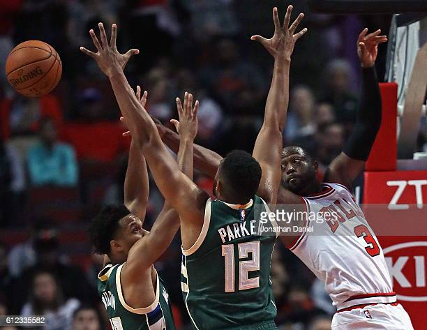 Dwyane Wade of the Chicago Bulls passes the ball under pressure from Malcolm Brogdon and Jabari Parker of the Milwaukee Bucks during a preseason game...
