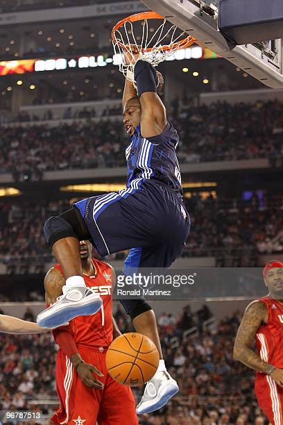 Dwyane Wade of the Eastern Conference hangs on the rim after dunking against Amar'e Stoudemire and Carmelo Anthony of the Western Conference during...