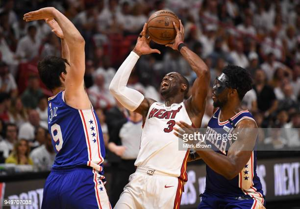 Dwyane Wade of the Miami Heat attempts to drive to the basket as he is surrounded by Dario Saric and Joel Embiid of the Philadelphia 76ers in the...