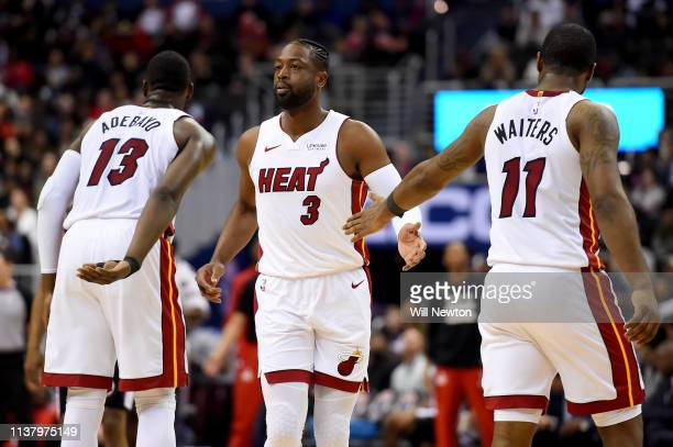 Dwyane Wade of the Miami Heat celebrates with Bam Adebayo and Dion Waiters of the Miami Heat after a play against the Washington Wizards during the...