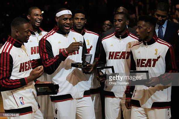 Dwyane Wade of the Miami Heat Chris Bosh of the Miami Heat and LeBron James of the Miami Heat look at their 2012 NBA Championship rings following a...