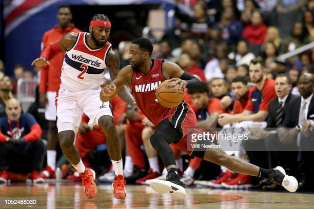 Dwyane Wade of the Miami Heat dribbles past John Wall of the Washington Wizards during the second half at Capital One Arena on October 18 2018 in...
