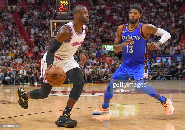 Dwyane Wade of the Miami Heat dribbles past Paul George of the Oklahoma City Thunder during the game between the Miami Heat and the Oklahoma City...