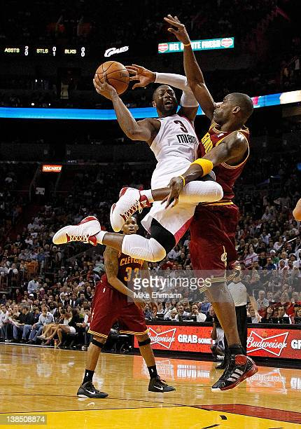 Dwyane Wade of the Miami Heat drives against Antawn Jamison of the Cleveland Cavaliers during a game at American Airlines Arena on February 7 2012 in...