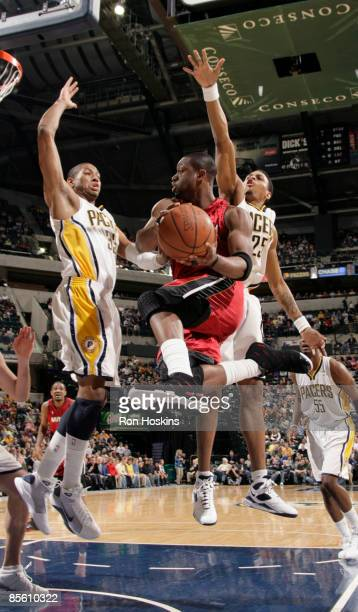Dwyane Wade of the Miami Heat drives against Danny Granger and Brandon Rush of the Indiana Pacers at Conseco Fieldhouse on March 25, 2009 in...