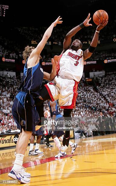 Dwyane Wade of the Miami Heat drives for a shot attempt against Dirk Nowitzki of the Dallas Mavericks during Game Three of the 2006 NBA Finals June...