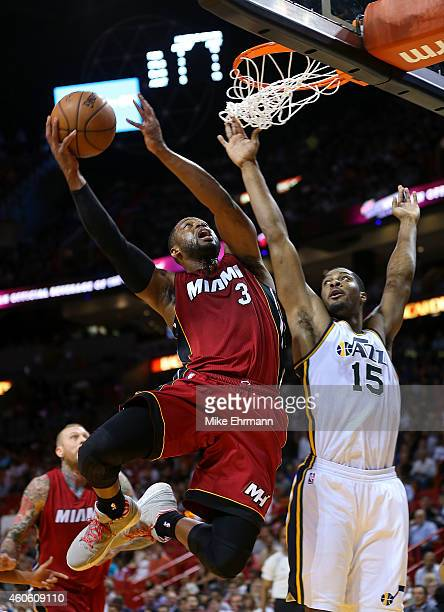 Dwyane Wade of the Miami Heat drives on Derrick Favors of the Utah Jazz during a game at American Airlines Arena on December 17 2014 in Miami Florida...